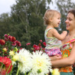 Mother with baby in flowers — Stock Photo