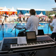 Synthesizer saxophone musicians pool — Stock Photo