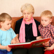 The grandmother and grandsons read the book — Stock Photo