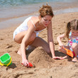 Mother with baby on beach — Stock Photo