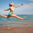 The girl in a jump about the sea — Stock Photo