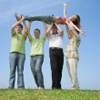Stock Photo: Four friends have lifted girl upwards