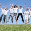 Seven friends in white T-shorts are in a jump — Stock Photo
