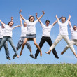 Seven friends in white T-shorts swing hands in a jump — Stock Photo