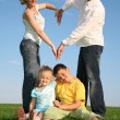 Family making heart. grass sky — Stock Photo