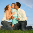Kissing family grass sky — Stock Photo
