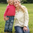 Mother and daughter on the grass - Stock Photo