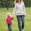 Mother and daughter walk on the grass - Stock Photo