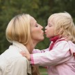 Girl and mother kiss — Stock Photo