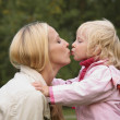Girl and mother kiss - Stock Photo