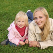Mother and daughter lie on the grass 2 - Stock Photo