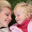 Mother and daughter lie on the grass and look at each other — Stock Photo