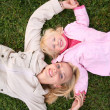 Mother and daughter lie on the grass and look upward 3 — Stock Photo #7436487