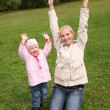 Mother and daughter sit on the grass and raised hands upward - Stock Photo