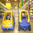 Children in the toy automobiles in the store - 图库照片