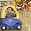 Child in the toy automobile in the supermarket - 图库照片