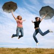 Two young women jump with the umbrellas — Stock Photo