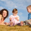 Mom with the children on the grass — Stock Photo #7436660
