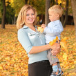 Blue-eyed blond with the son in the park in autumn — Stock Photo