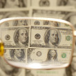 Dollars by the closeup through the eyeglasses — Stock Photo