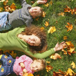 Woman with the son and the daughter they lie on the grass — Stock Photo #7437018