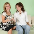 Two girlfriends with glasses on sofa — Stock Photo