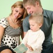 Child with book and parents — Stock Photo