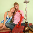 Couple sit on pillow and smoke hookah — Stock Photo #7437209