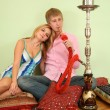 Couple sit on pillow and smoke hookah — Stock Photo