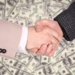 Handshaking on dollar background — Stockfoto