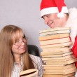 Santa Claus with a lot of books and blonde — Stock Photo
