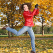 Girl in the red jacket jumps in the park in autumn — Stock Photo