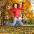Girl in the red jacket jumps in the park in autumn 2 — Stock Photo