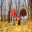 Family goes for a walk in the park in autumn — Stock Photo