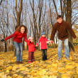 Father and mother with the children in the park in autumn — Stock Photo #7437910