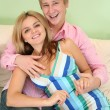 Young couple on sofa in green room — Stock Photo