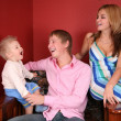 Young family laughing in red room — Stock Photo