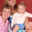 Smiling young family in red room — Stock Photo #7438409