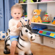 Little boy in playroom on toy zebra — Stock Photo