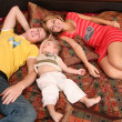 Family lies on red carpet on sofa — Stock Photo #7438501