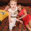 Parents with child on carpet 2 — Stock Photo #7438507