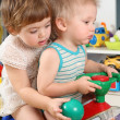 Two children in playroom on toy scooter — Stock Photo