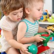 Two children in playroom on toy scooter - Foto Stock