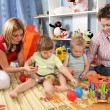 Two mothers play with children in playroom - Stock Photo