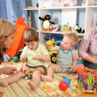 Two mothers play with children in playroom 2 — ストック写真