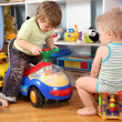 Two children in playroom with toy scooter — Stock Photo