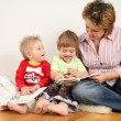 Children looking books with mother - Stock Photo