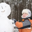 Stock Photo: Boy makes snowman 2