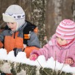 Boy and girl paly in forest in winter — Stock Photo