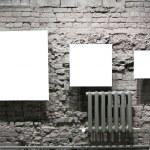 Three blank frames on grey brick wall — Stock Photo #7439001